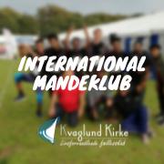 Mænd står opstillet med løbenummere. Billedet er sløret og på den står der International Mandeklub. Billedet indeholder et link som omdirigerer til begivenhed.