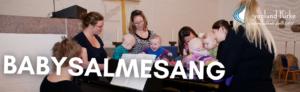 Billedet viser 5 babyer og deres mødre. Babyerne ligger på klaveret. Yvonne organist sidder og spiller på klaveret.